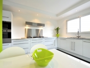 Klassische L-Form Küche mit stilvollen grünen Akzenten