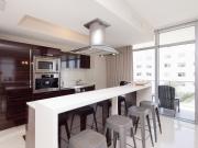Offene Wohnküche mit Hochglanzfronten in Holzoptik