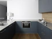Klassische U-Formküche mit blauen Acrylfronten