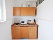 Kleine Singleeinbauküche mit klassischen Holzfronten