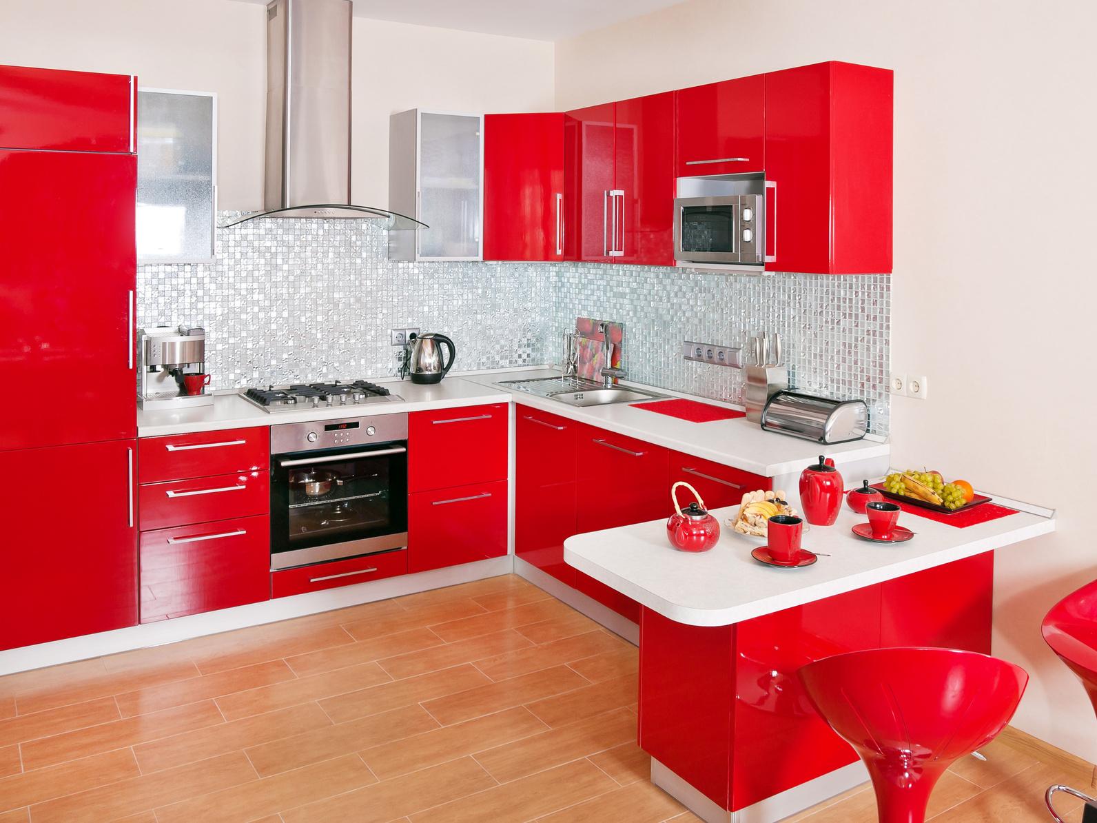 Eine Kleine Rote Hochglanzküche In U Form Mit Kleinem Sitzbereich.