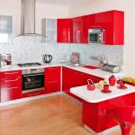 Eine kleine rote Hochglanzküche in U-Form mit kleinem Sitzbereich.